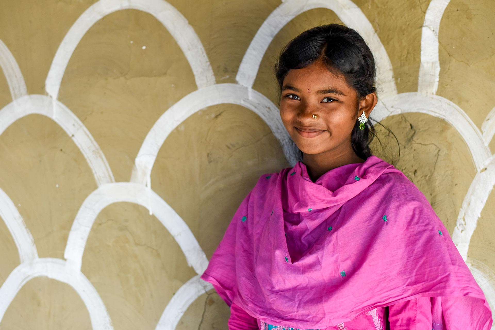 A girl stands against a white beige patterned wall. She's wearing a pink shawl and other bangladeshi attire.
