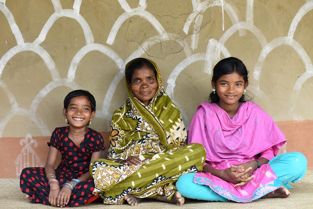 Two bangladeshi girls sit beside their mother