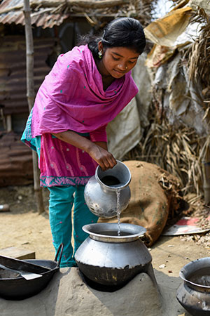 A bangladeshi girl helps her mother by getting water for cleaning. She pours water from a silver basin into a container on the ground.