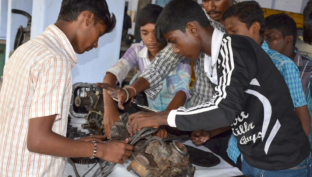 Indian teenagers work on a small motor.