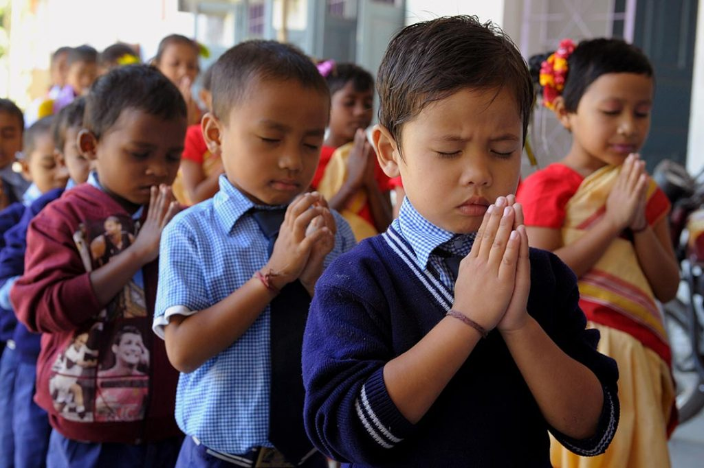 Young, Indian boys stand in class, with their hands folded to pray.