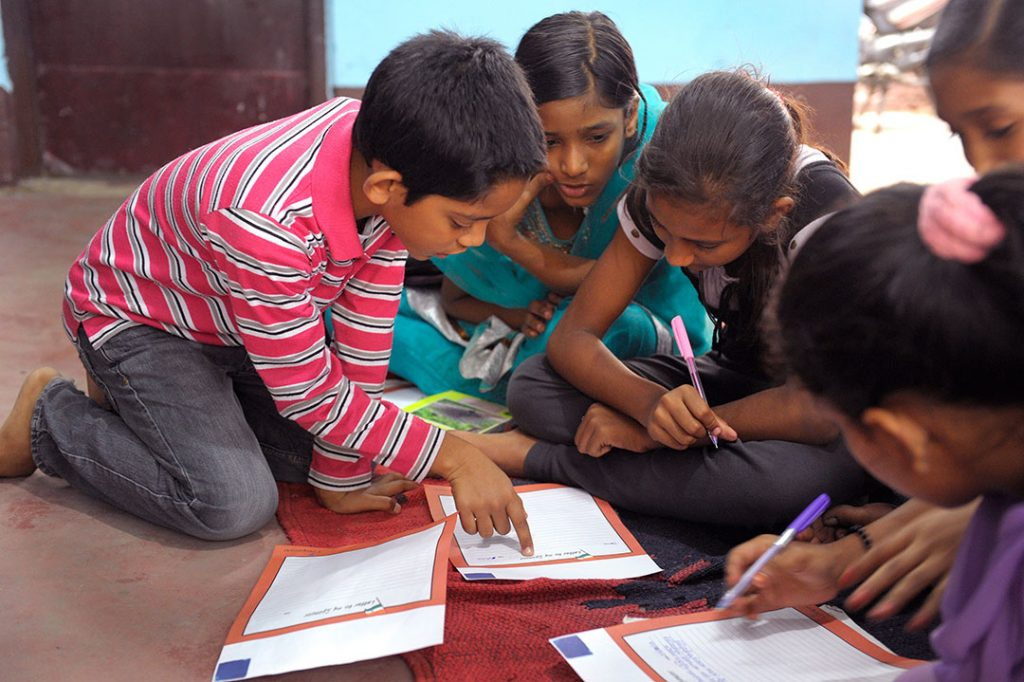 Indian children kneel around their work books and talk about their assignment.