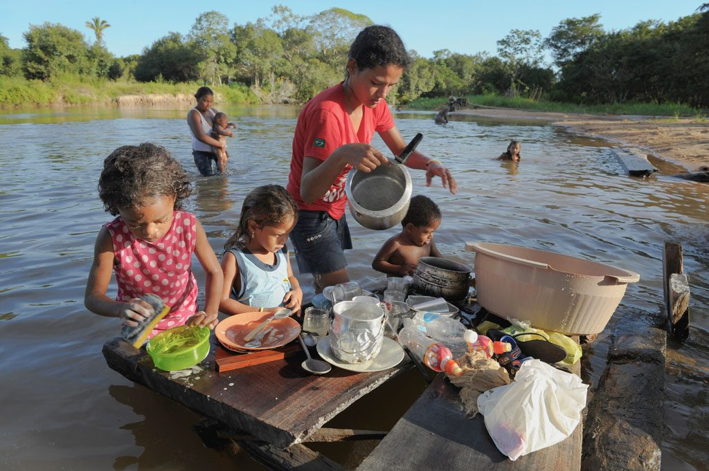 Ana and Thayna Franca de Almeida work with their mother and brother in the water. They are washing plates, pots, and pans in the water. They are using buckets, a bar of soap, and sponge. There is another woman with two other children in the river behind them.