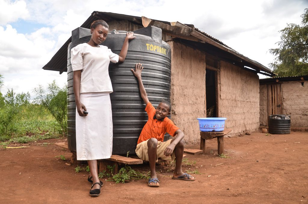 Thirteen-year-old Eric Njuki, a young teen boy, wearing an orange shirt and khaki shorts, at home, with his mother, Rose Nduta, adult female wearing a white shirt and skirt, are standing with a Compassion-provided water tank to harvest rain water, large black water reservoir, container. A walled mud home and greenery is in the background.