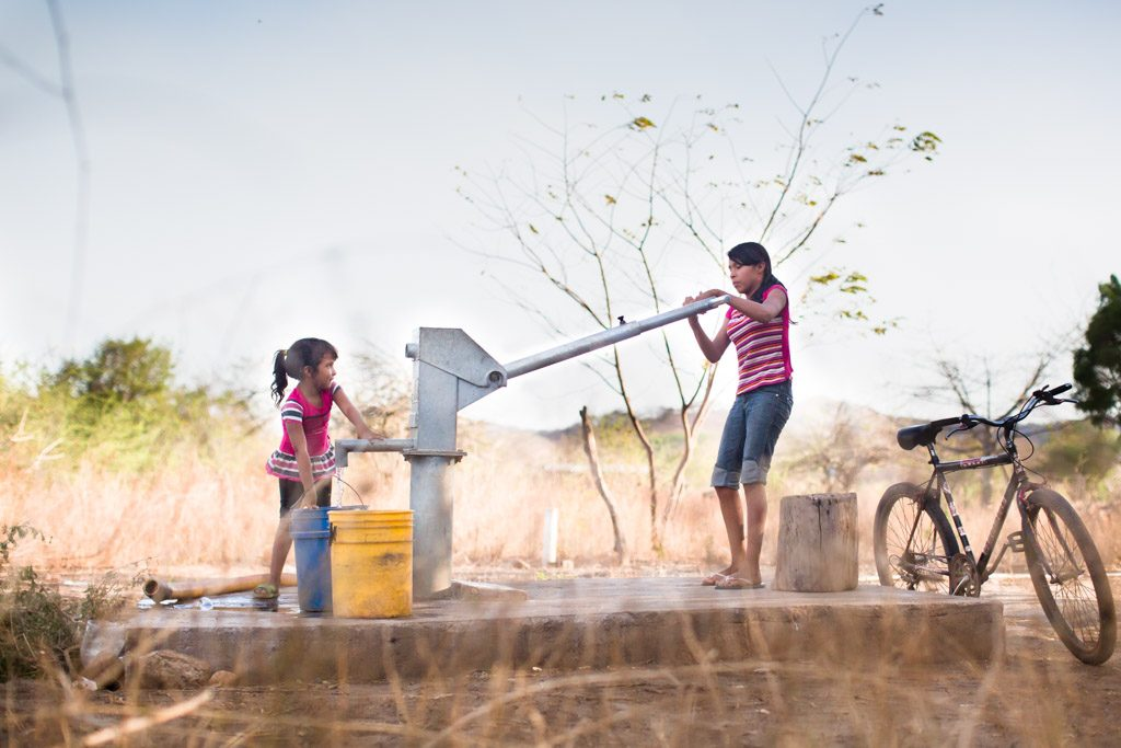 Two children working together to get water from a well. A bike, bicycle is to the right.