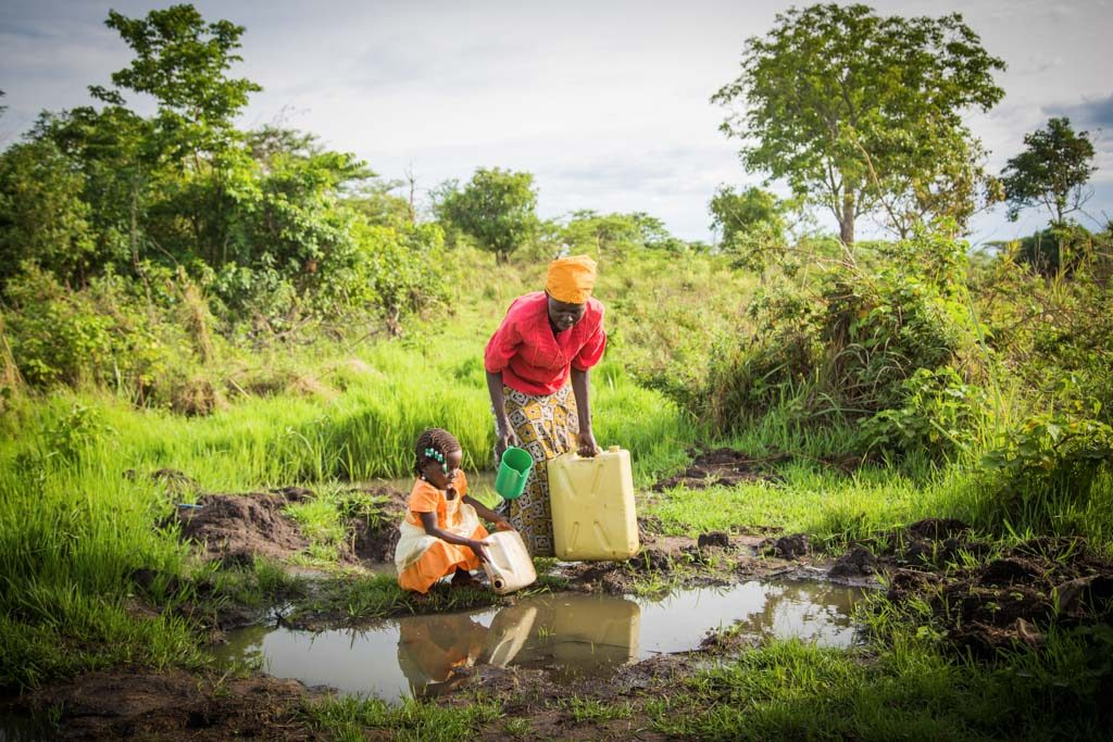 Betty, a girl, child, wearing an orange and white dress, bends over to fetch water with a plastic container beside her mother as they are getting water in plastic buckets and containers, daily household chores, parent, adult woman, Evelyn, who is wearing a yellow scarf, turban, head wrap on her head, a red shirt and long pattern skirt, together at a small water source, large puddle, large mud puddle of collected rain water on the ground, with the mother using a green cup in her hands to retrieve the water to pour into the containers. This appears to be an unsanitary water source, potentially unhealthy, unsafe, and not clean drinking water in a large puddle on the ground. They are surrounded by trees in the background, and dark mud on the ground and grass.