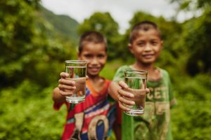 Two boys hold up clear glasses of water. The boys are out of focus and the background is lush jungle.