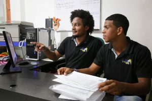 Francisco Meza Ardila, 18 years old, teenager, teen, boy, wearing a black shirt, sits at a desk and computer, with stacks of papers, and with the child development center staff, Compassion staff, adult man, tutor, helping to work at the computer monitor at the center.