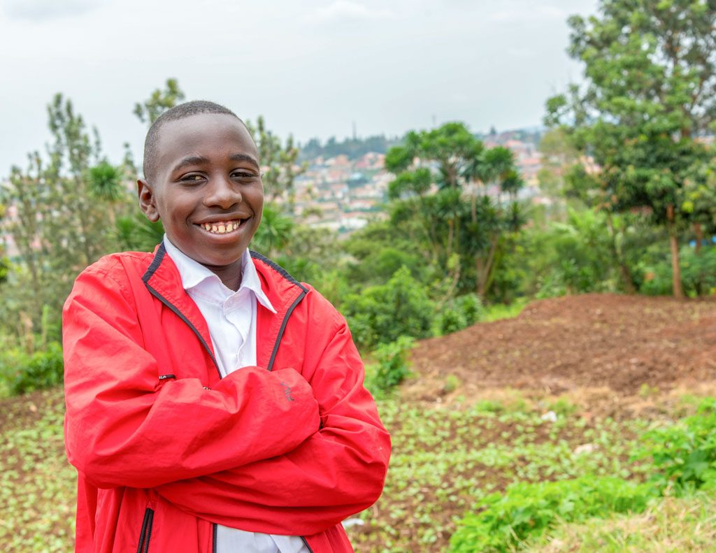 A Rwandan boy wearing bright red jacket, stands with his arms crossed and smiles at the camera.