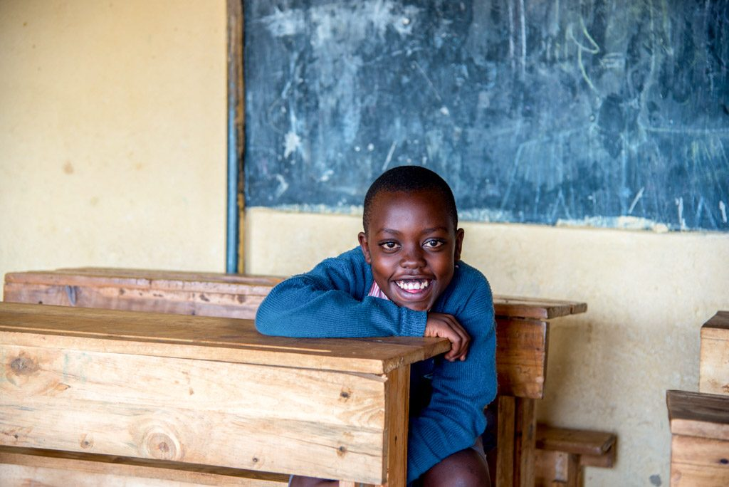 A boy sits a wooden school desk in a classroom and smiles at the camera.