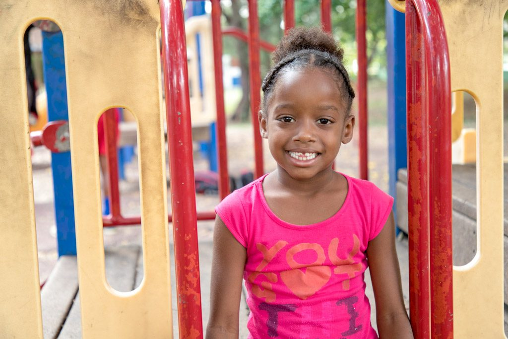 A girl in a pink t-shirt sits on a playground and smiles at the camera.