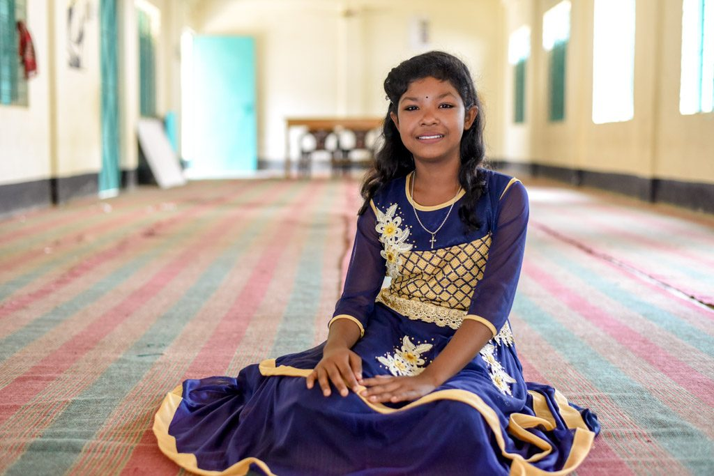 A girl sits on the floor in a large room. She wears an ornate dress and smiles.