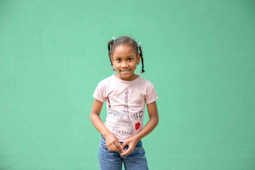 A young girl stands in front of an emerald green wall. She wears a pink t-shirt with the Eiffel tower on it, she wears jeans.