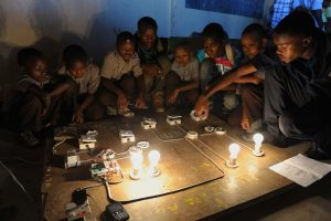 A group of boys, teenagers, teens, youth, sitting around a large on the ground circuit board and lights, learning electricity, staring down, learning vocational lessons and skills.