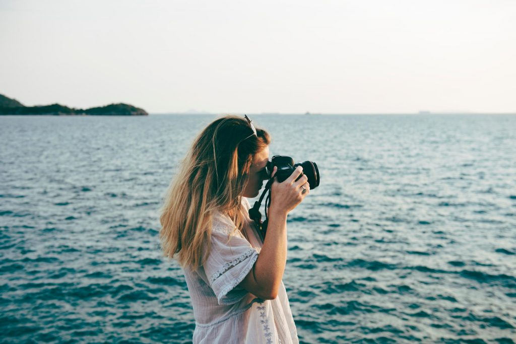 A woman stands by the water and takes a photograph.