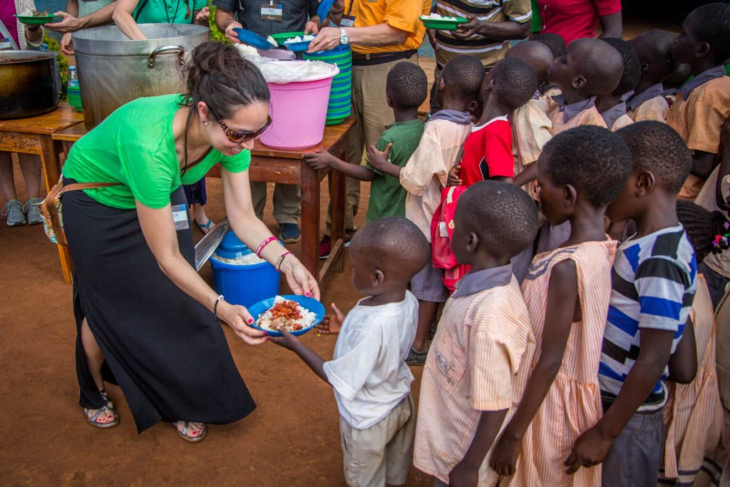 A female sponsor wearing a green shirt and black skirt is smiling while she offers a plate full of food to a young boy wearing a white shirt and tan pants, uniform. A group of children wearing uniforms form a crowded line behind the boy. A group of sponsors are helping, preparing in the background.