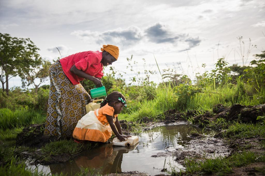 Mother and child fetch water behind their home. Betty, a girl wearing an orange and white dress, bends over to fetch water with a plastic container beside her mother as they are getting water in plastic buckets and containers. Evelyn, who is wearing a yellow scarf, turban, head wrap on her head, a red shirt and long pattern skirt, together at a large mud puddle of collected rain water on the ground, with the mother using a green cup in her hands to retrieve the water to pour into the containers. This appears to be an unsanitary water source, potentially unhealthy, unsafe, and not clean drinking water in a large puddle on the ground. They are surrounded by green trees and grass.