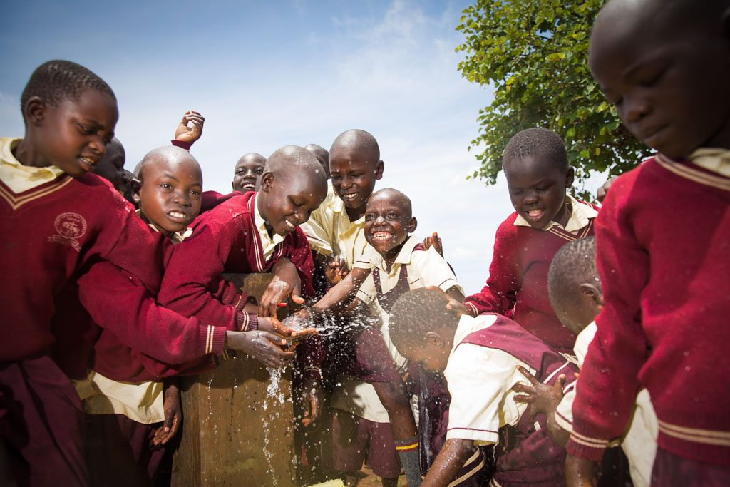 A group of children gather happily together, boys and girls, dressed in school center uniform clothes, red and white dresses or sweaters and shirts, as they are splashing water, clean safe drinkable sanitary pouring water from outside water source, outdoor water faucet.