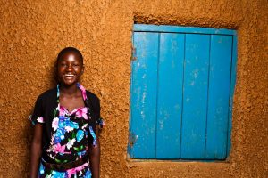 A laughing, smiling girl in a colorful floral shirt stands in front of an orange wall with a wooden blue window, shutter to the side.