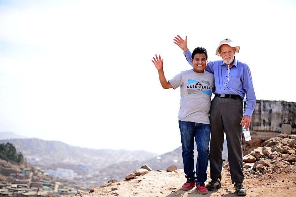 Andrew stands with his sponsor on the top of a hill. They both wave.