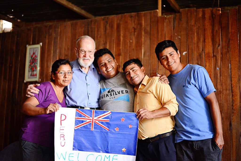 Andrew's sponsor stands with his family in their home.