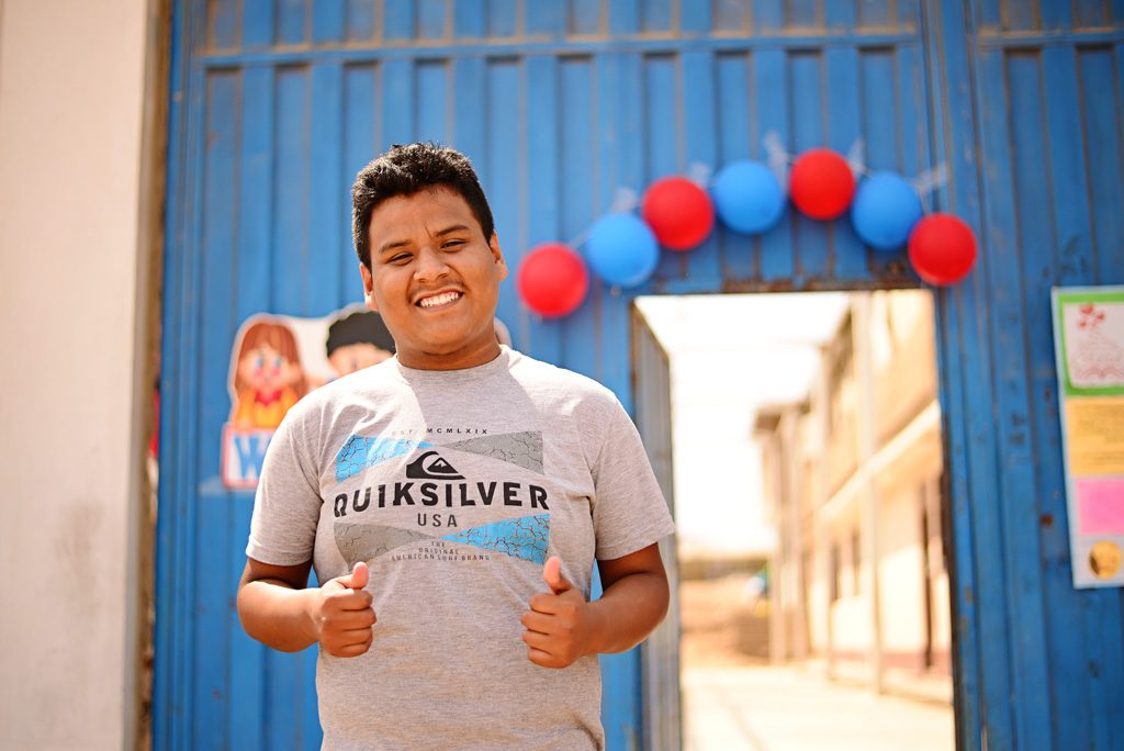A young man stands in front of a blue wall with balloons on it. He wear a gray, quicksilver shirt and give two thumbs up.