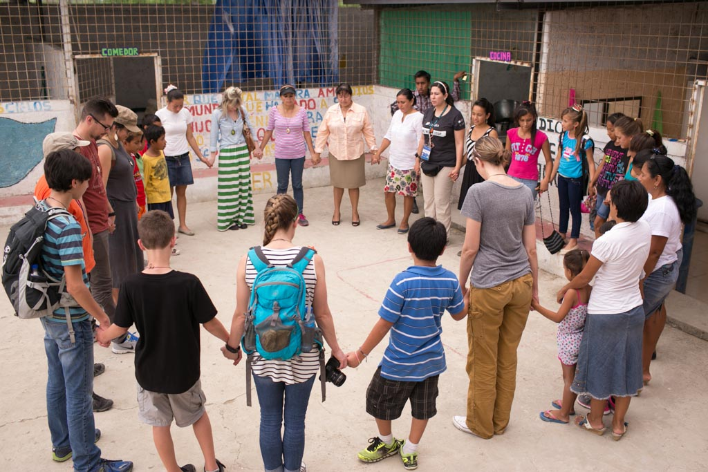 Visiting sponsors, visitors, adult men and women, parent, mothers and fathers, with their children, sons and daughters, families, stand together in a large circle holding hands and praying, prayers, with each other during a prayer time at the center.