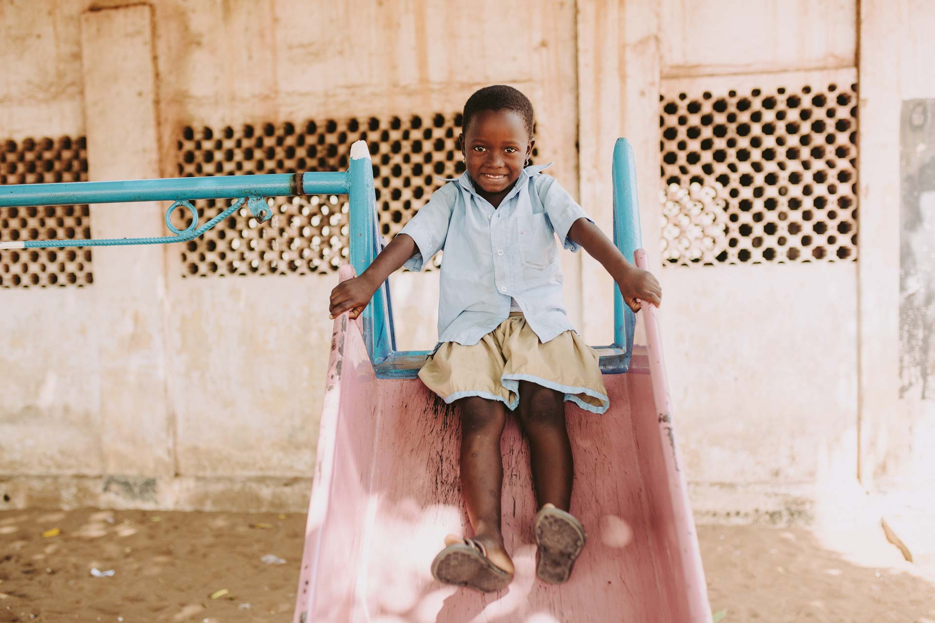 Aklobessi, girl, child, wearing a blue shirt, brown skirt, small earrings, smiles as she is playing, play time, play, sliding down the slide outside at the center on the playground equipment.