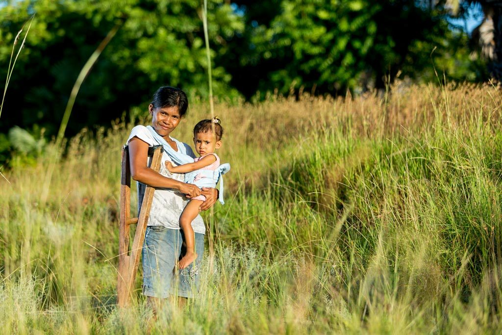 A mother, wearing a baby carrier in her shoulders, walks in a tall grass countryside with her wood crutch, holding a baby, in her arms, posing outside with her child and green trees in the background.