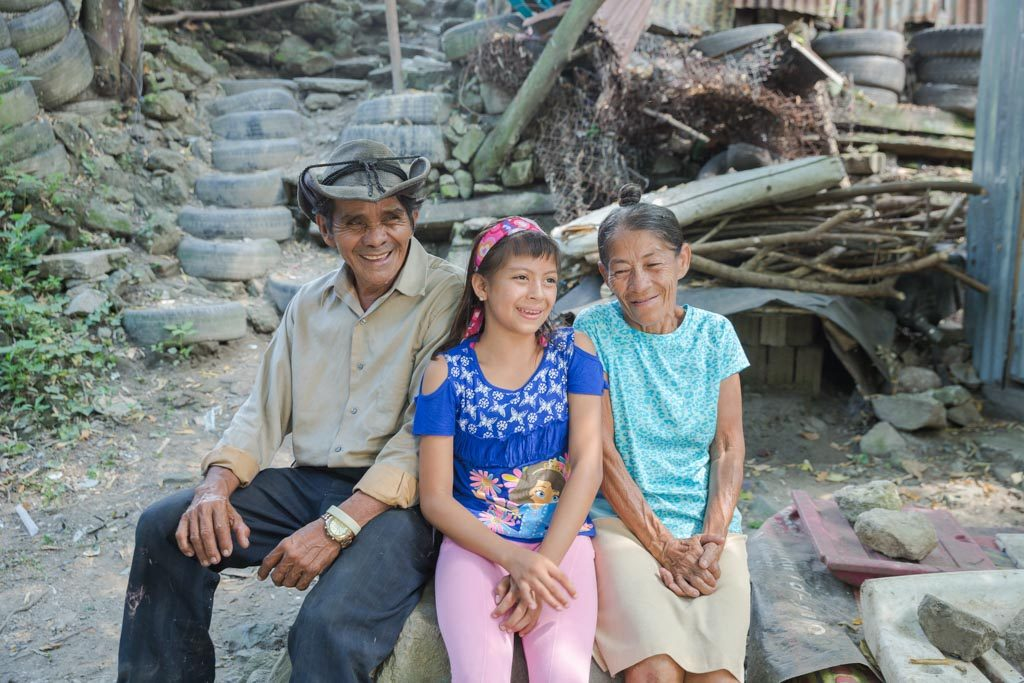 A girl, wearing a blue shirt, pink headband in her hair, and pink pants, sits outside on a large rock with her grandparents near their home.