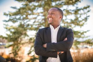 A man stands with his arms crossed as he looks out of frame. He smiles, seeming happy and proud.