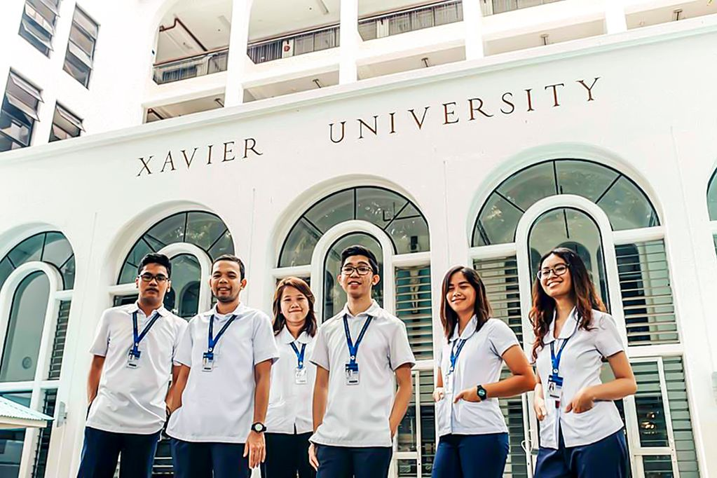 "A group of six students stand outside wearing matching white shirts in front of a white building that is labeled ""Xavier University"""