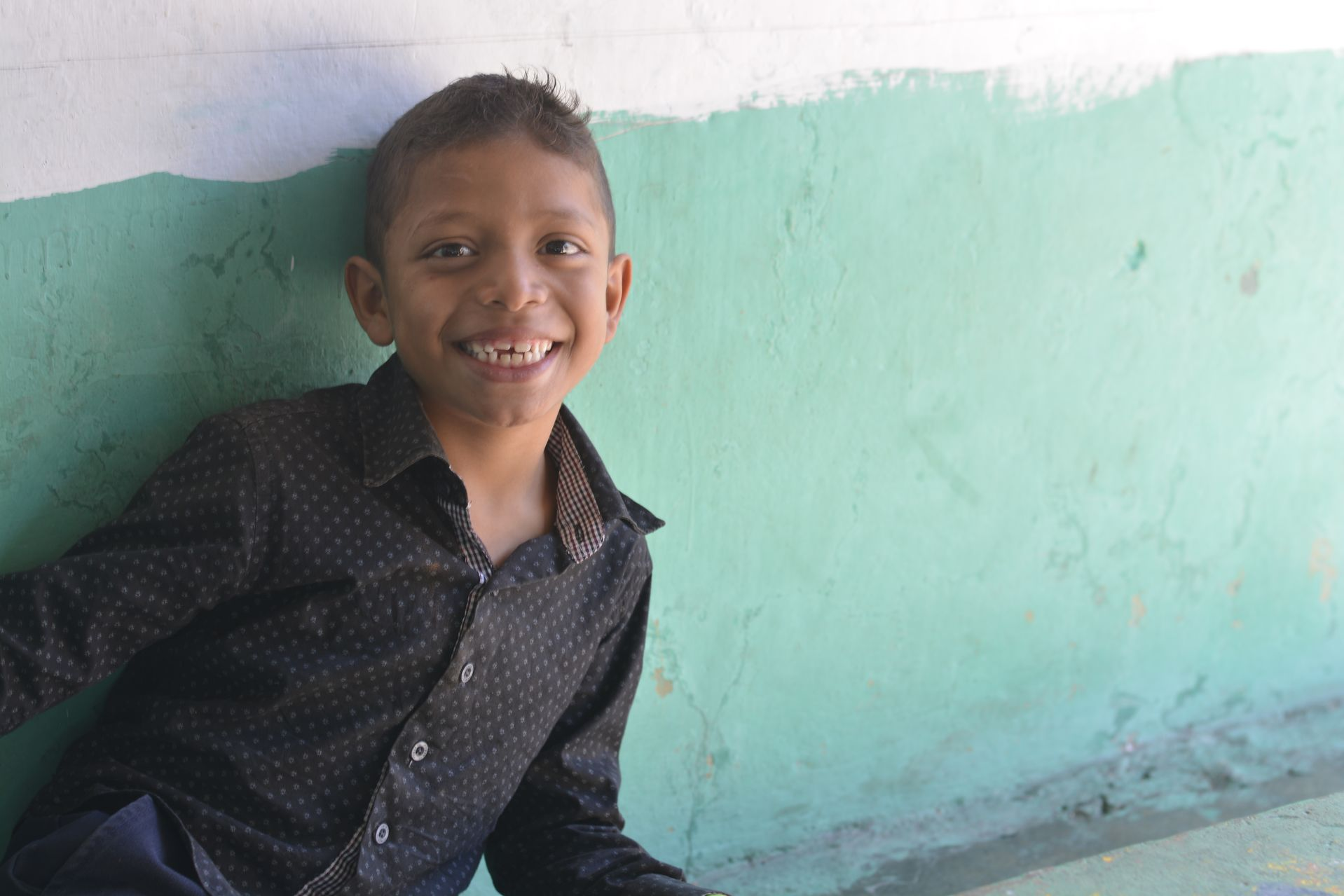 A young boy wearing a black shirt smiles in front of a green and white wall