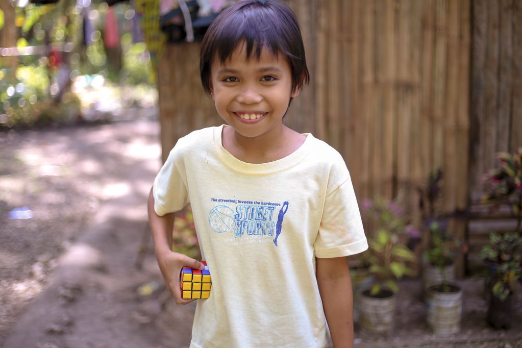 A smiling 10 year-old boy, male child, Jessie Mhar Villaplana, wearing a yellow shirt, is holding his Rubik's cube. He is standing in front of a wooden, bamboo wall, fence and several potted plants.