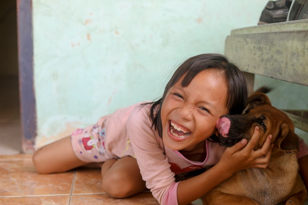 A little girl, female child, wearing a pink shirt is posing, playing with her dog named Kopi at her terrace.