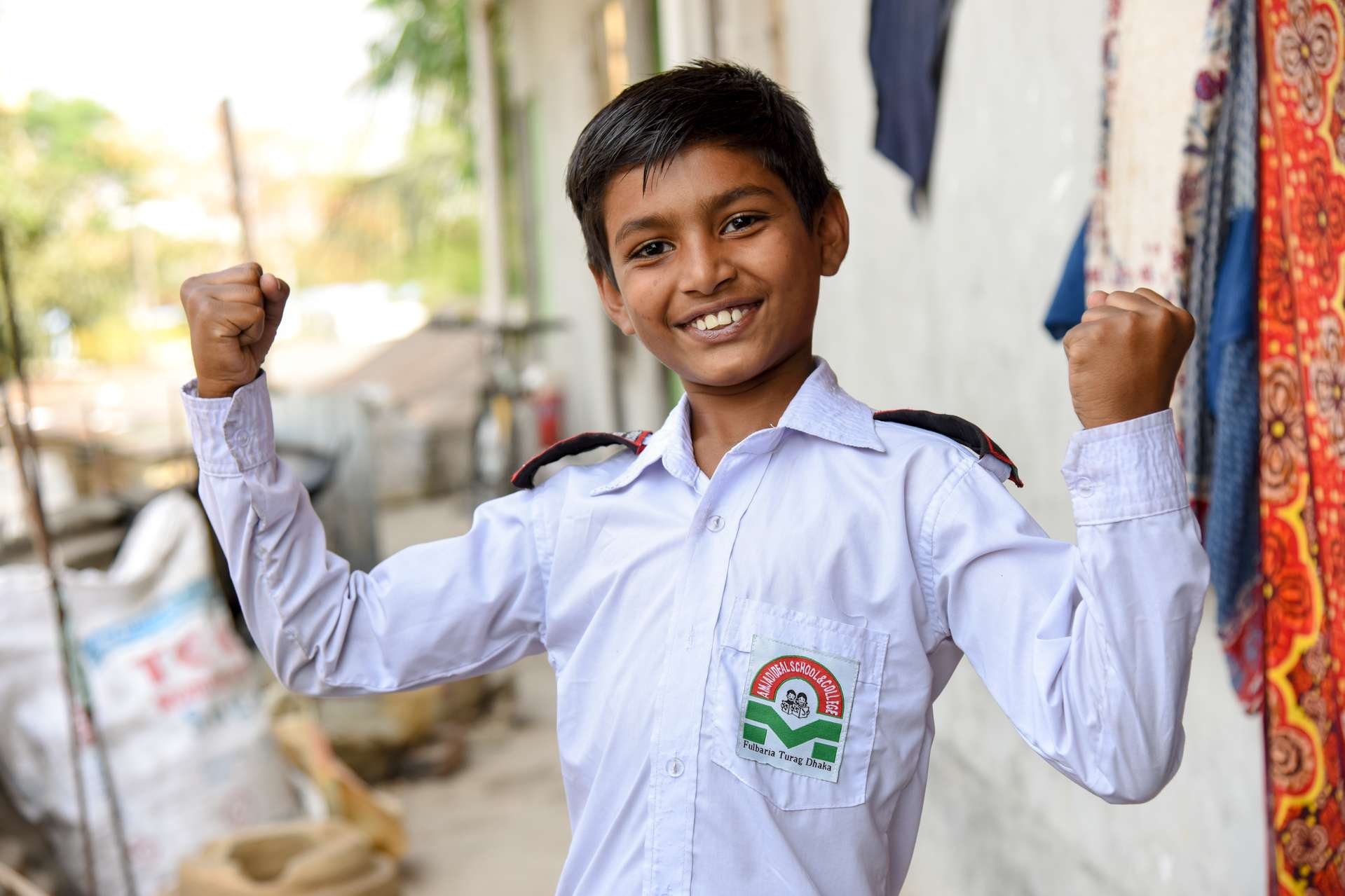 Boy flexes his muscles and shows off his uniform shirt.