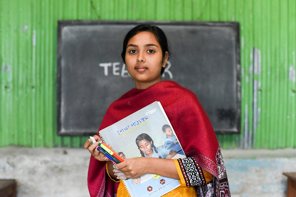 A teenage girl wearing red in Bangladesh stands in front of a blackboard holding a book and pens.