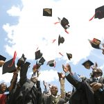 Graduates in Uganda wearing robes throw their graduation caps in the air.