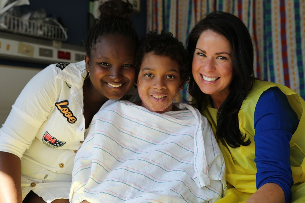 A boy in the hospital, covered by a blanket, sitting with his smiling sister and sponsor.