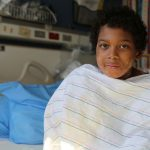 A boy sits in a hospital bed wrapped in a blanket