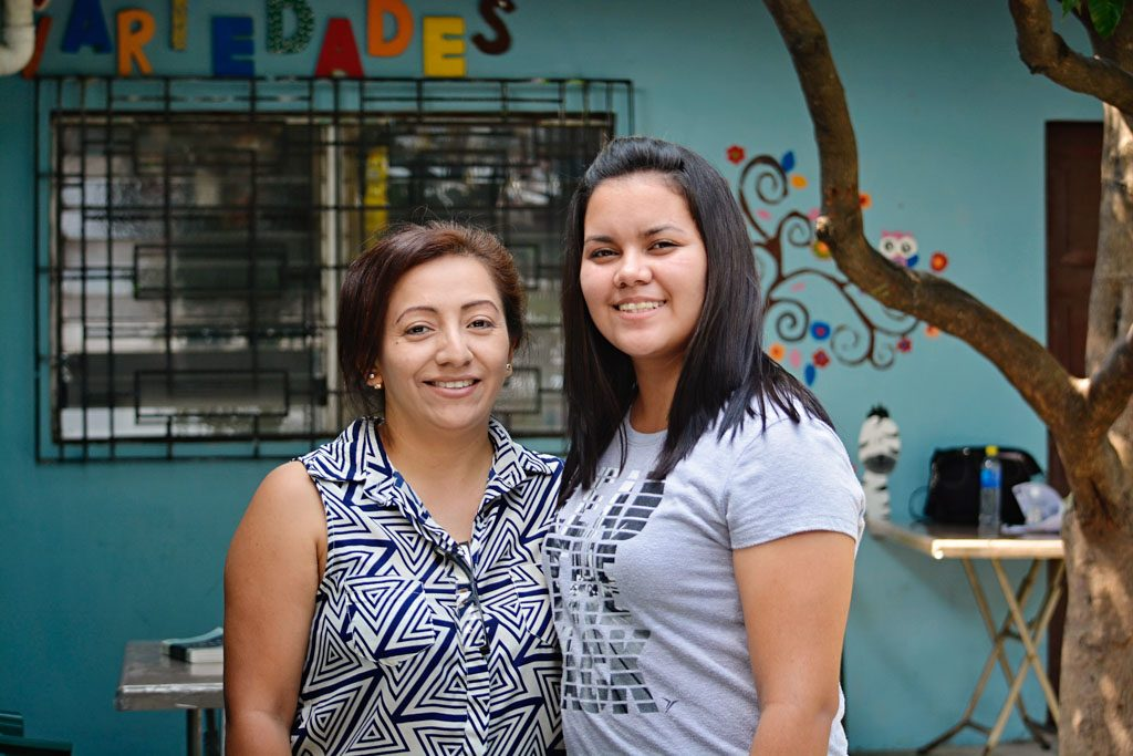 A yong woman stands next to her former tutor. They stand in a colourful classroom.