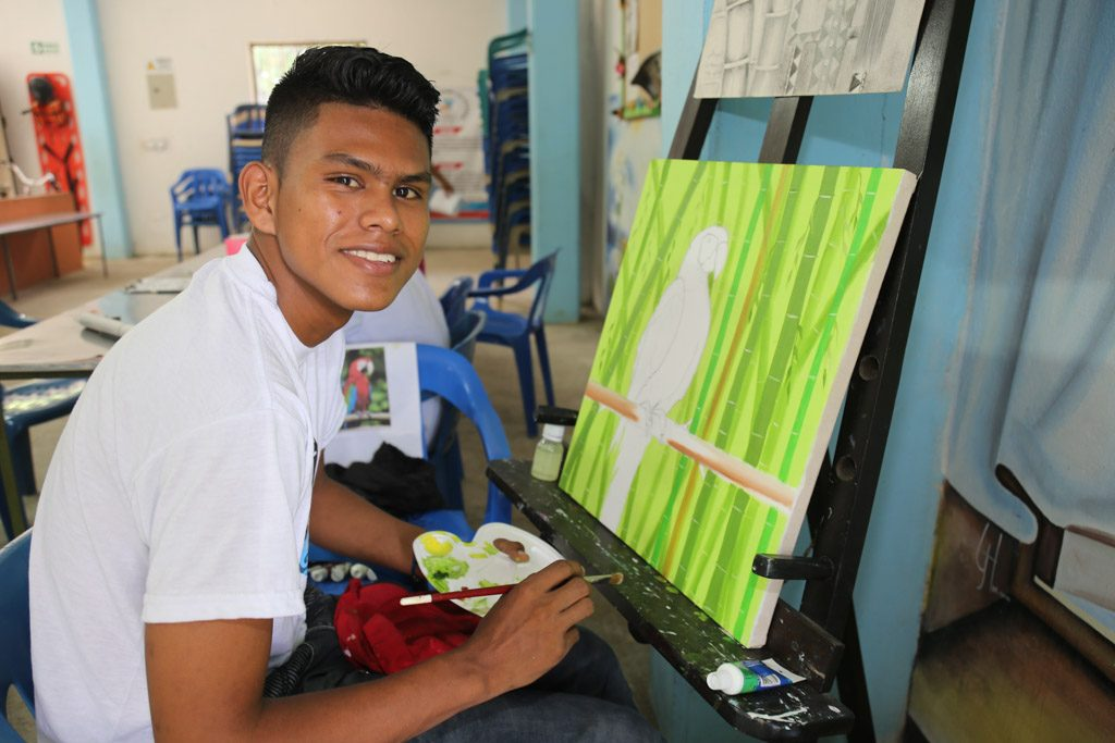 A young man sits infront of a paint canvas holding a paint brush and a paint palatte