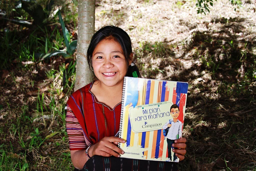 "A girl in Guatemala proudly displays her ""My Plan for Tomorrow"" workbook."