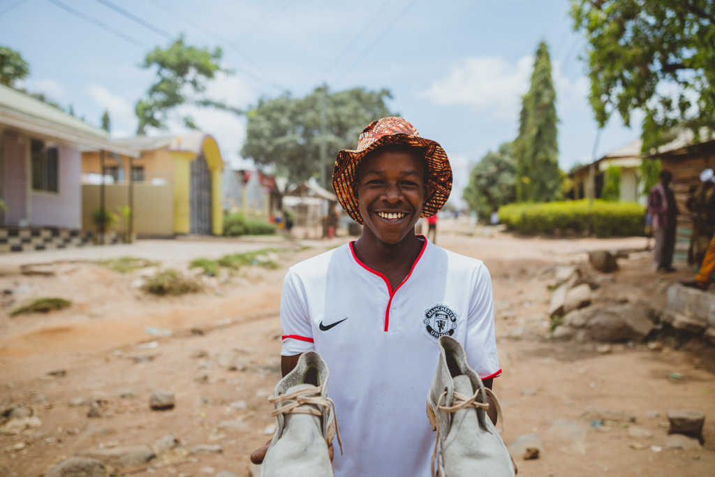 A young man from Tanzania holds up a pair of white shoes that he's made.