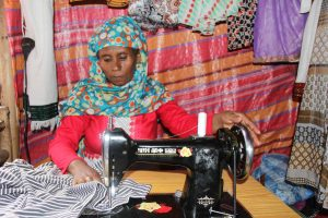 An adult woman, wearing a blue patterned head wrap, scarf over her head, hijab, covering her head and hair, sits at a black sewing machine, vocational skills, tailoring, stitching skills, sewing, working, labor on garments, clothes, making clothes, inside her small shop, market, store, with a red striped cloth behind her on the wall.