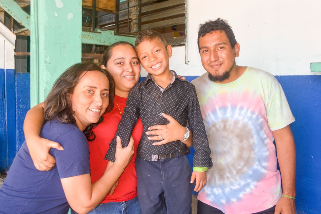 A boy in black is surrounded by three smiling adults, a woman in blue, a woman in red hugging the boy and a man in a tie-dye shirt