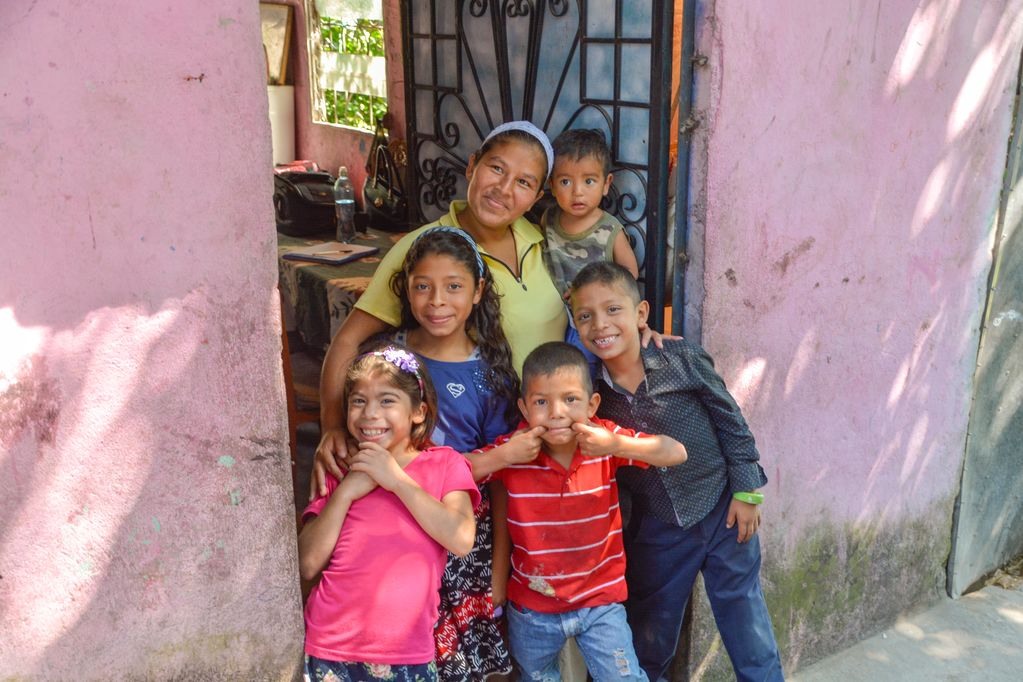 A woman in lime green stands in the doorway of a pink home holding a toddler and surrounded by four children.