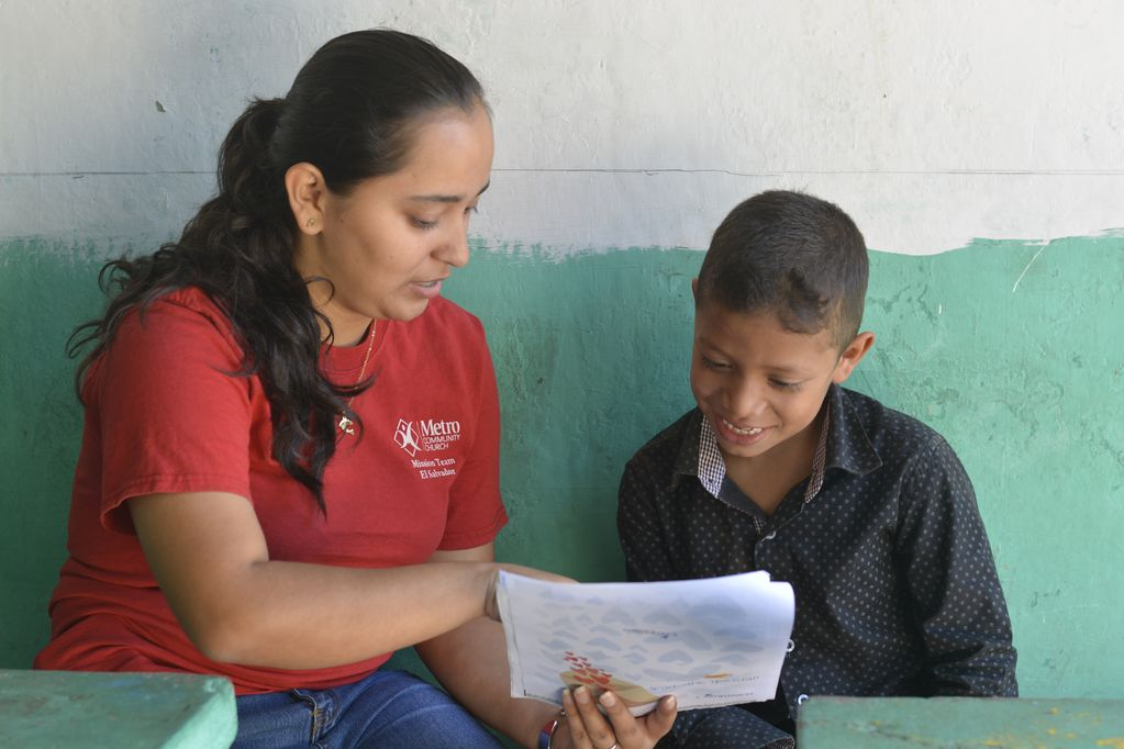 A woman in red sits next to a boy in black pointing at a letter and reading it to him.