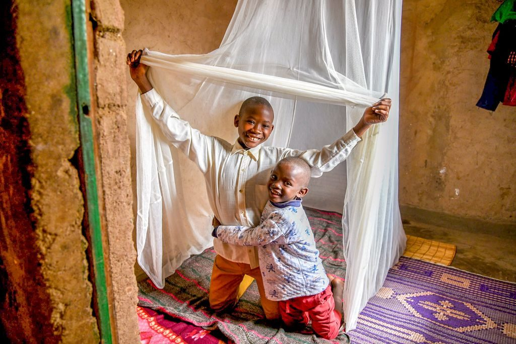 Two brothers smile under their mosquito net and bed