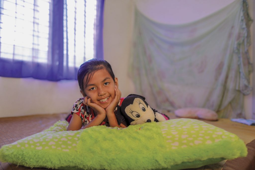 8- year-old girl lies on her pillow with a stuffed animal, smiling and posing for the camera.